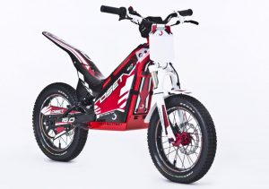 "Have you ever wanted to just ride right out of your garage or build a makeshift course in your backyard? Well, Oset bikes has made this possible without getting your neighbors all in an uproar. The 2016 20.0 48v Racing Electric Trials Bike is designed for 8-12 year old's (but don't let that stop you from trying it out if you're North of that age by 25-30 years) and is powered by 48v battery system (four 12 volt batteries), that has lasted us up to 2-3 hours per ride time, depending on size of rider and how it is ridden. The Oset 20.0 bike comes with a 48v wall charger that takes up to four hours to charge when unit is fully drained. The 20.0 2016 model comes with three fully adjustable power settings (speed, power, and response). Each setting can be adjusted via a knob near the front of the machine. What I have learned is that ""speed"" is the overall top speed the Oset 20.0 will go, ""power"" is much like a torque adjustment similar to bottom end on a gas powered machine, and ""response"" is how quick you want the throttle to hit when accelerating (similar to rpm response on a gas powered machine). For those in the target age range, the Oset 20.0 is a machine, which is a lot of fun, provides incredible opportunities for gaining skills, and the bike can be ridden in a decent-sized backyard – without upsetting your not so dirt bike friendly neighbors. The Oset 20.0 machine is configured with front and rear disc brakes controlled by hand levers, like a mountain bike, a twist throttle like a motorcycle, and the direct-drive electric motor means there's no transmission, so no shift lever or clutch."